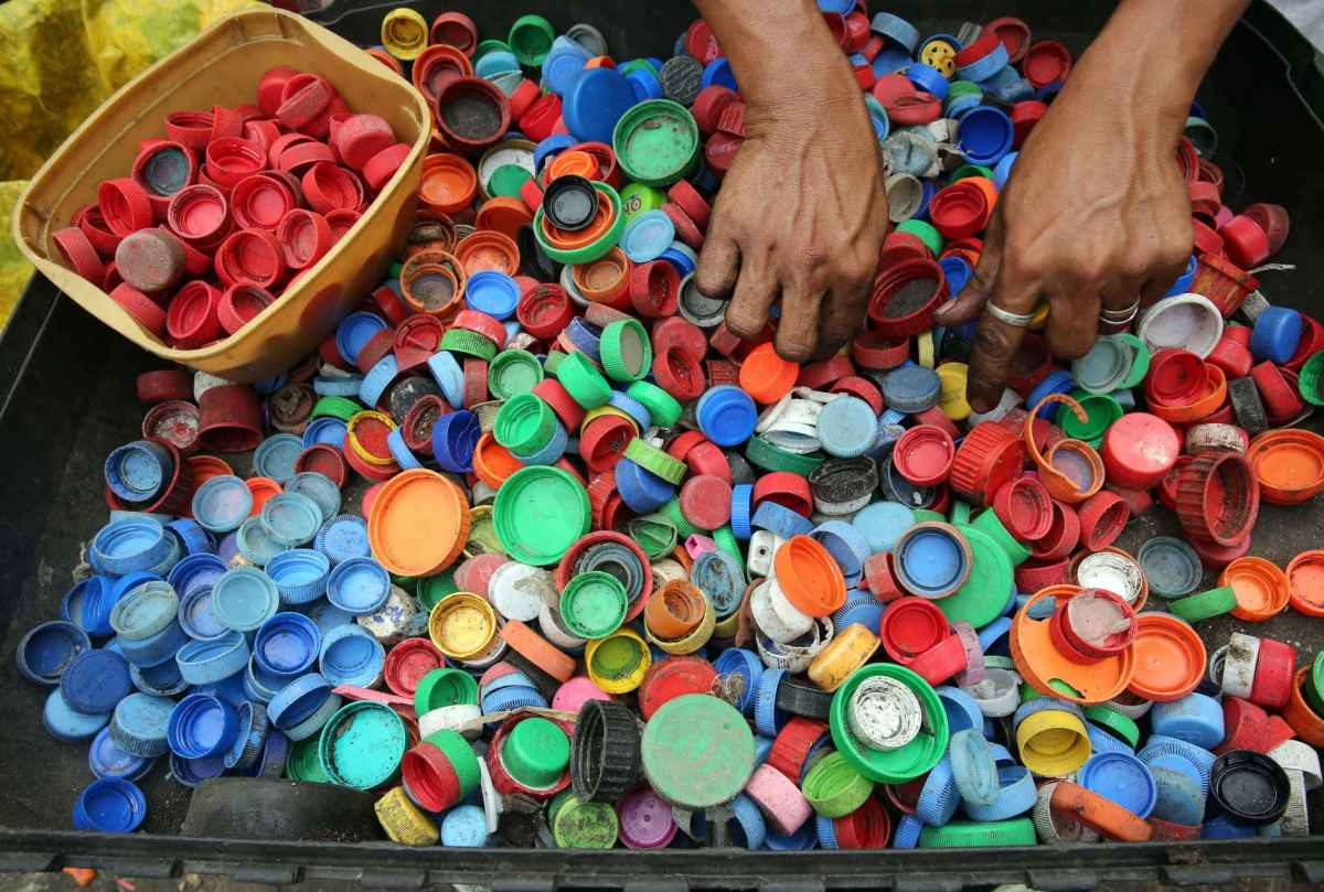 person hands on assorted color plastic lid lot